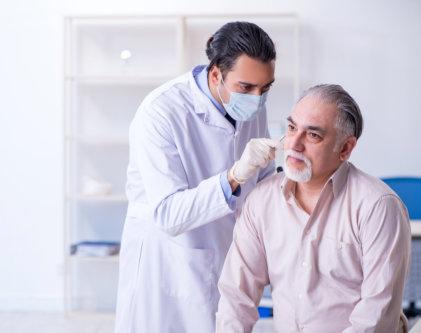 doctor checking senior mans ear