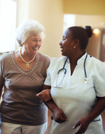 registered nurse and senior woman talking while walking