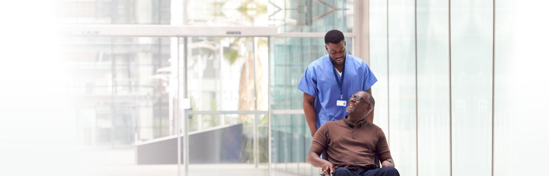 male caregiver assisting senior man in his wheelchair