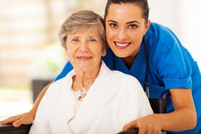 senior woman on wheelchair with nurse wearing stethoscope smiling