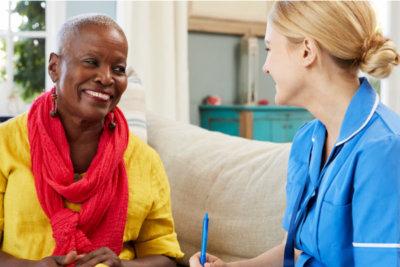 female nurse talking with senior woman smiling