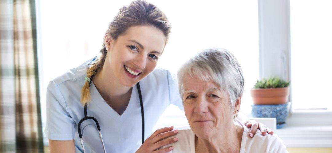 female nurse smiling while holding a senior