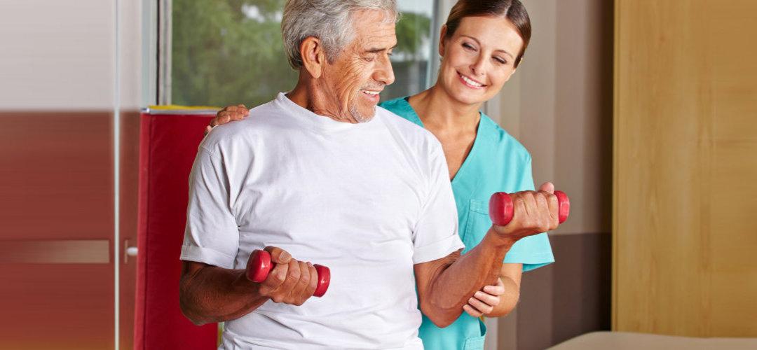 caregiver assisting senior man exercising with dumbbells