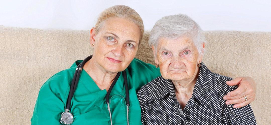 female registered nurse hugging senior woman