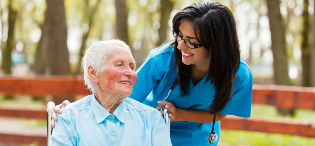 caregiver and senior man having a facilty tour outdoor